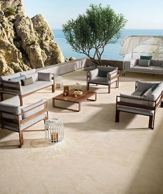Porcelain Paver Deck with elaborate patio furniture and beautiful background of trees, water and mountain.