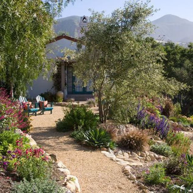 Scenic view of home with mountains in background, porch and decomposed granite walkway surrounded by trees, flowers and rock border.