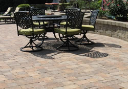 Wrought iron table and chairs on top of patio pavers.